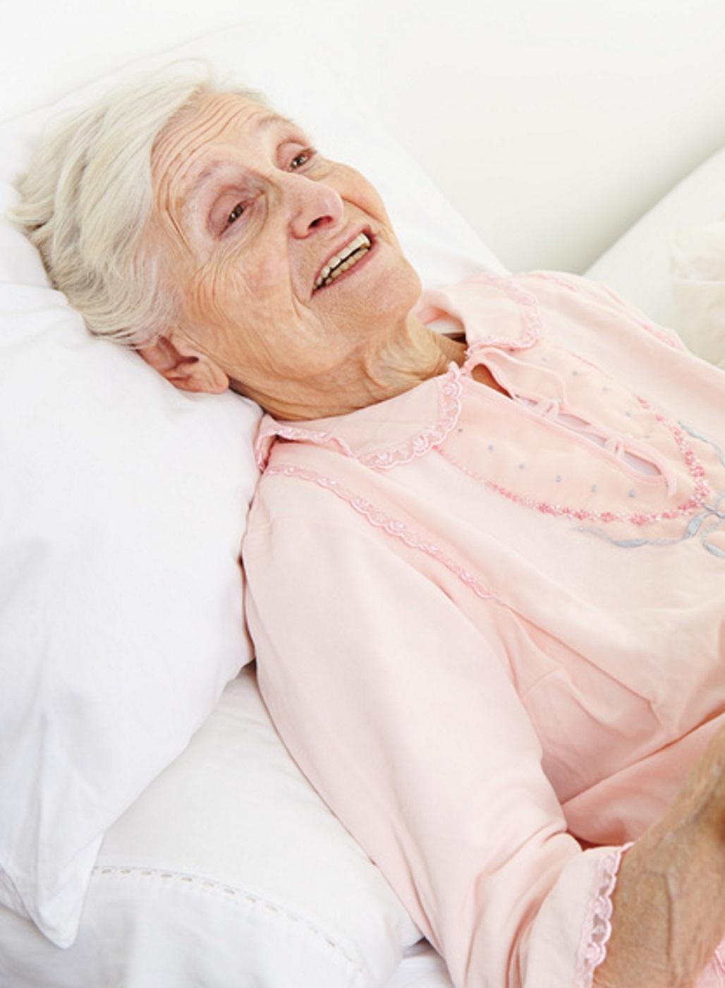 Alte Dame liegt im Krankenbett.