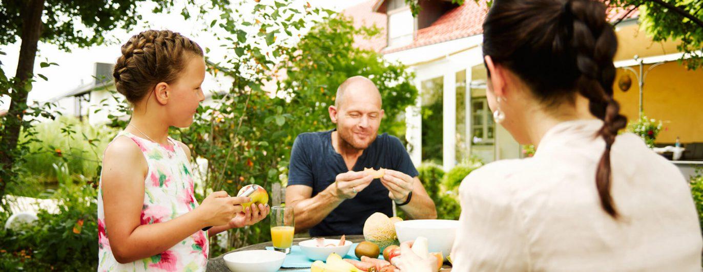 Familie im Garten beim Essen.