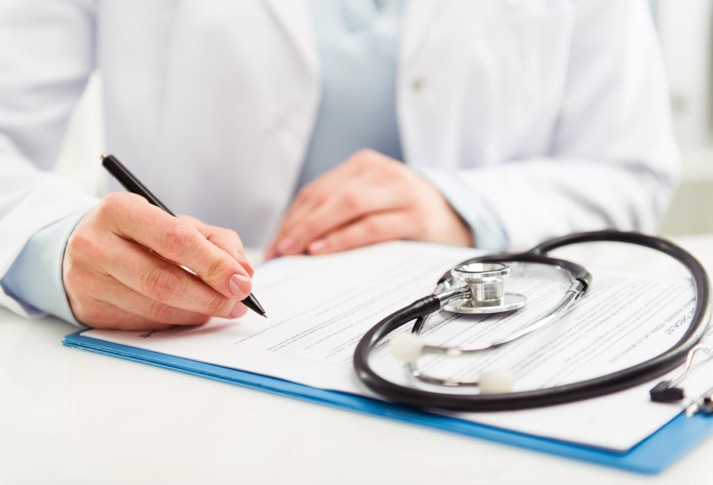 Arzt füllt einen Antrag aus.