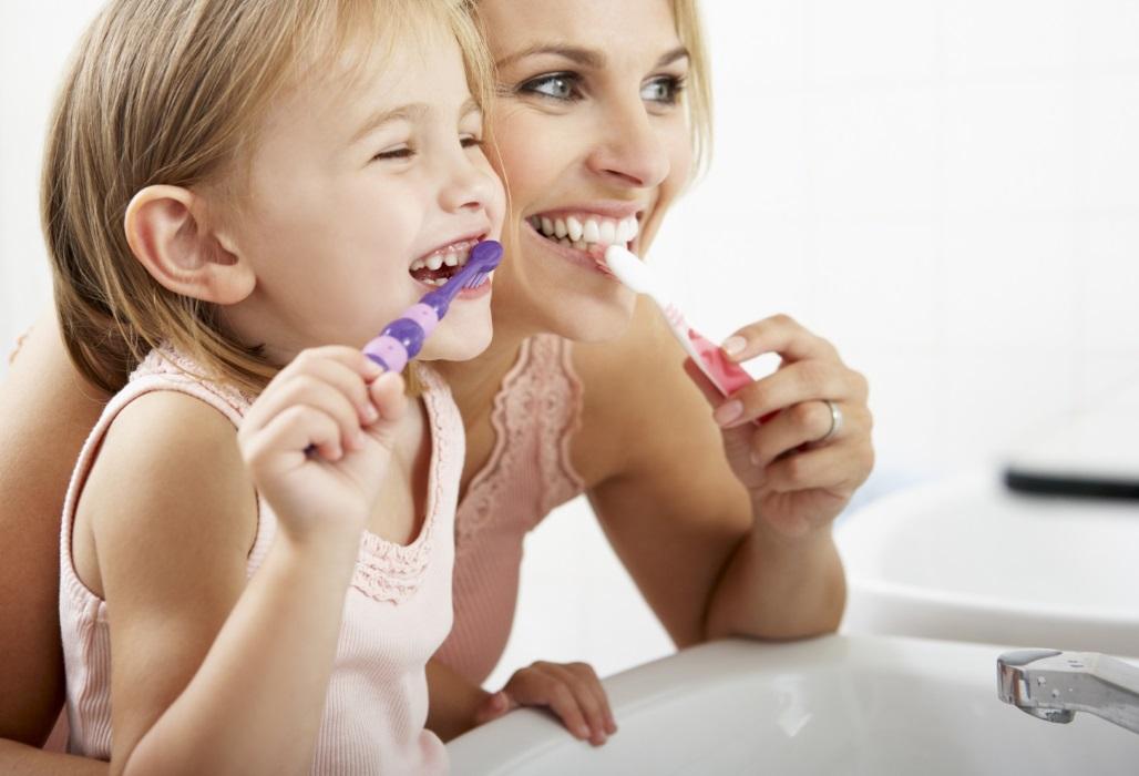 Mutter und Kind putzen sich gemeinsam die Zähne.