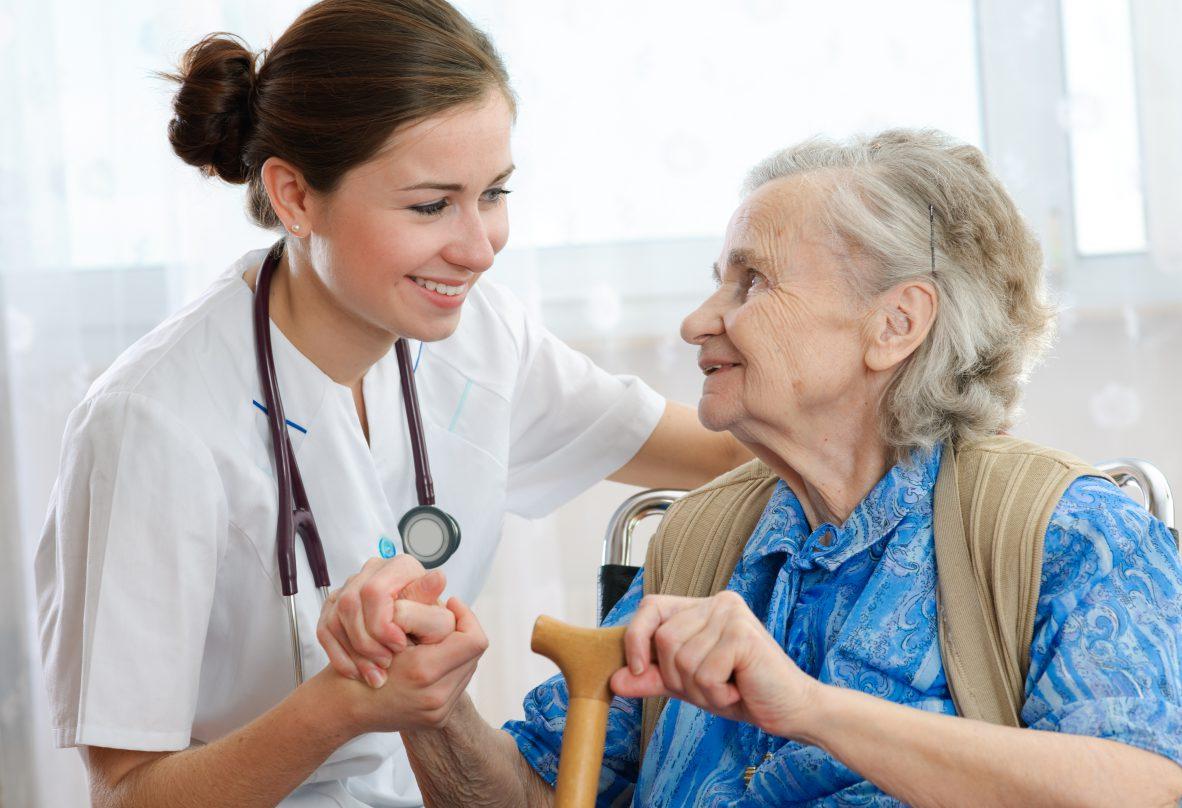 Ältere Dame wird durch eine Pflegerin betreut