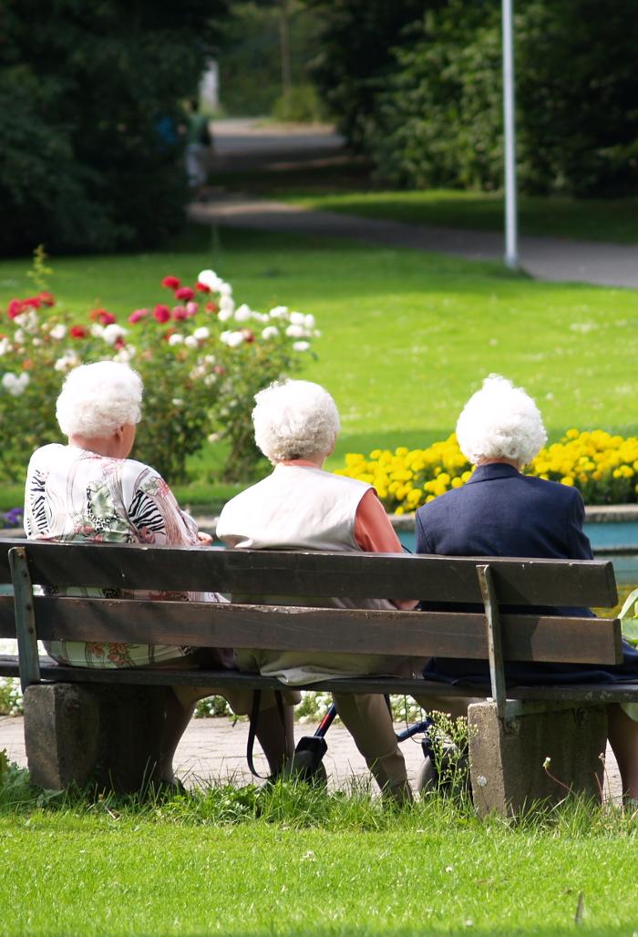 Ältere Damen sitzen auf einer Bank im Park.