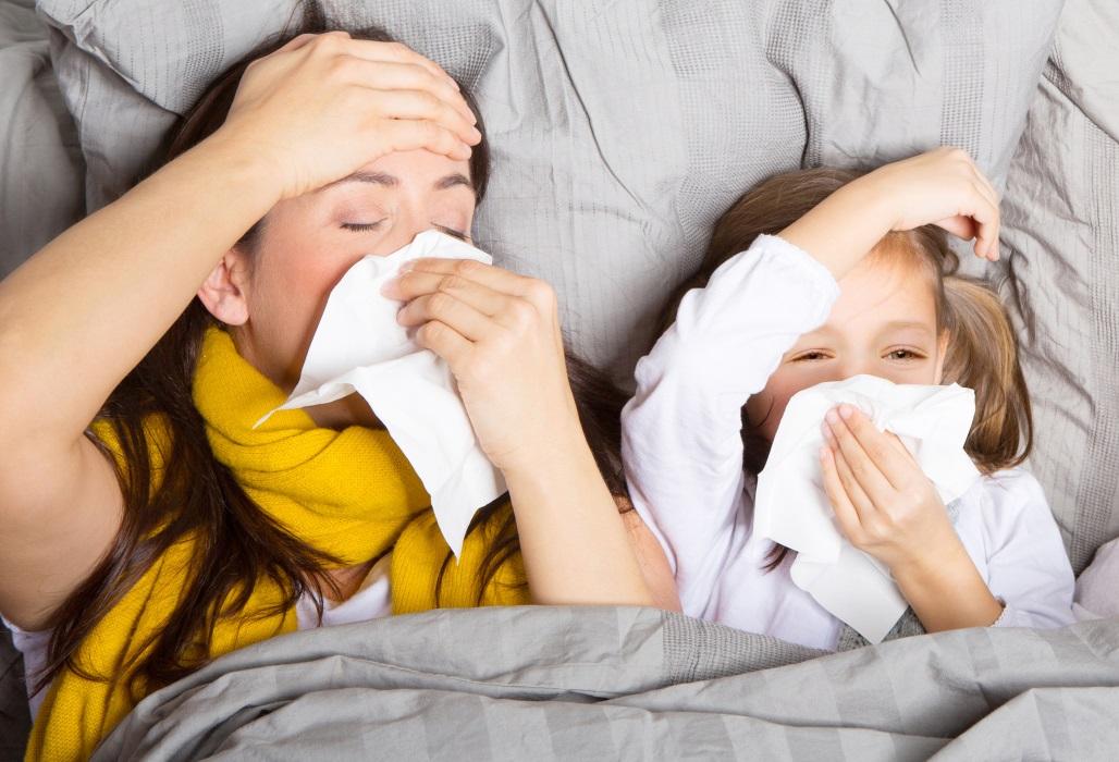 Mutter und Tochter liegen krank im Bett.