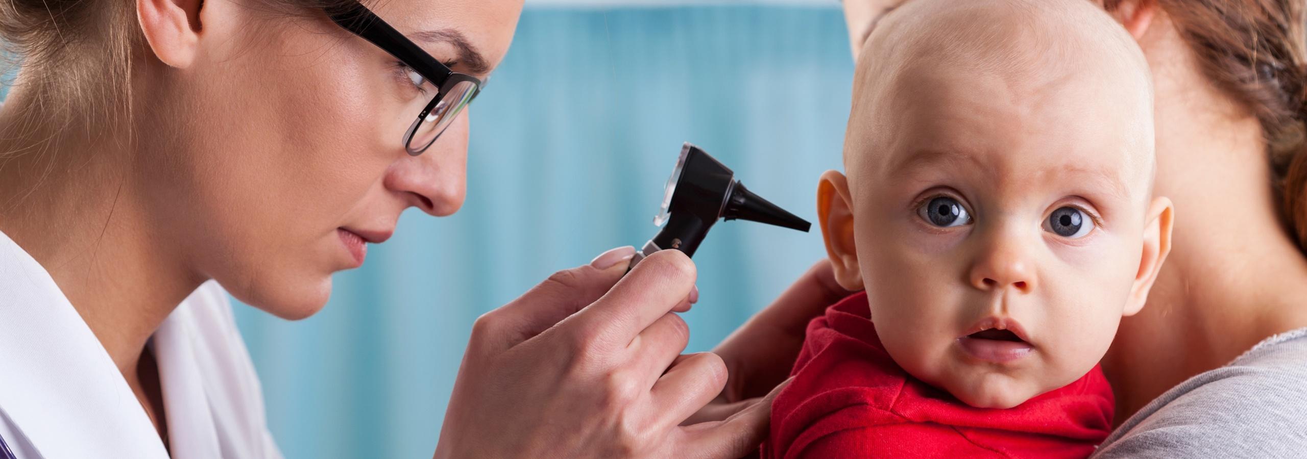 Ärztin untersucht die Ohren eines Babys.