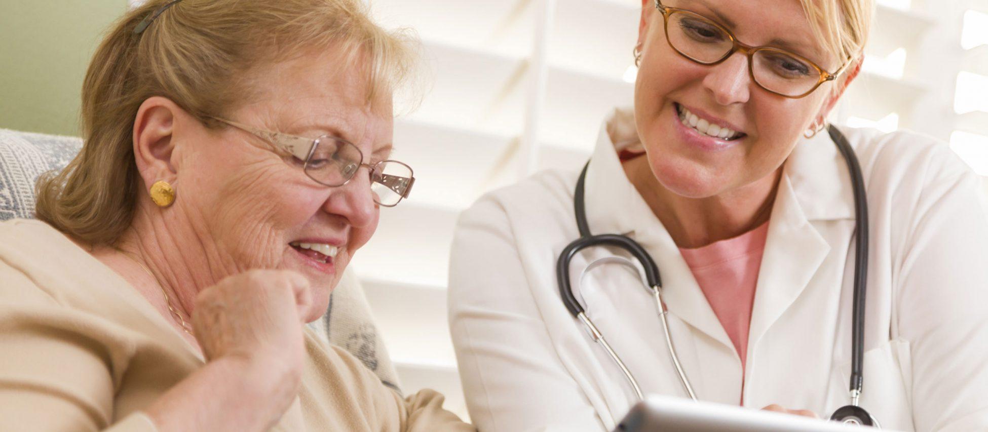 Ärztin zeigt einer Patientin etwas auf einem Tablet.