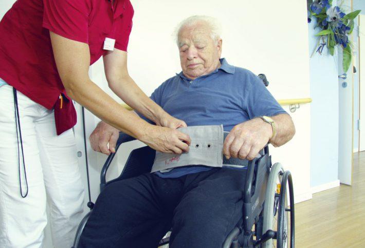 Ein älterer Herr wird im Rollstuhl festgegurtet.