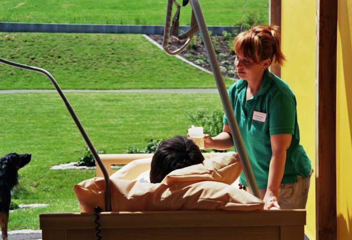 Pflegerin versorgt Mann ins einem Krankenbett. Der Blick des Kranken ist in den Garten gerichtet.