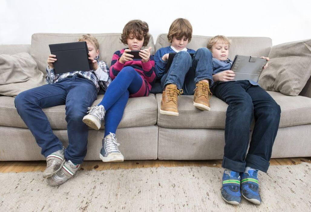 Kinder benutzen elektronische Geräte.
