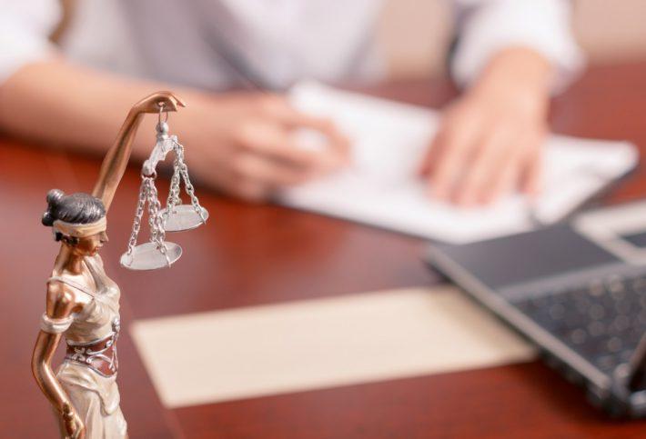 Mann am Schreibtisch, eine Justitia-Figur im Vordergrund.
