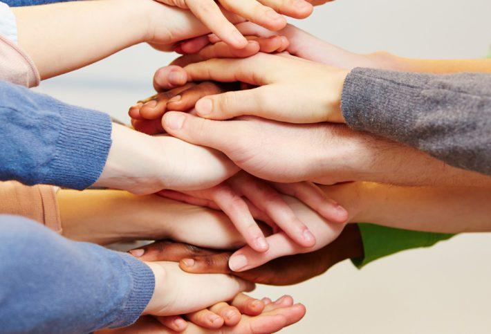Zusammenhalt - viele Hände als Stapel.