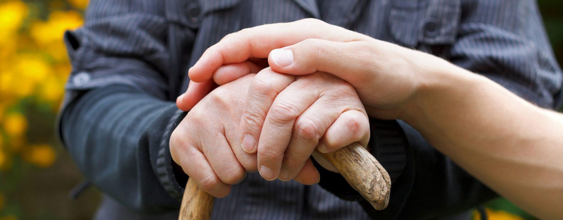 Eine Hand liegt auf den Händen eines ältern Herren.
