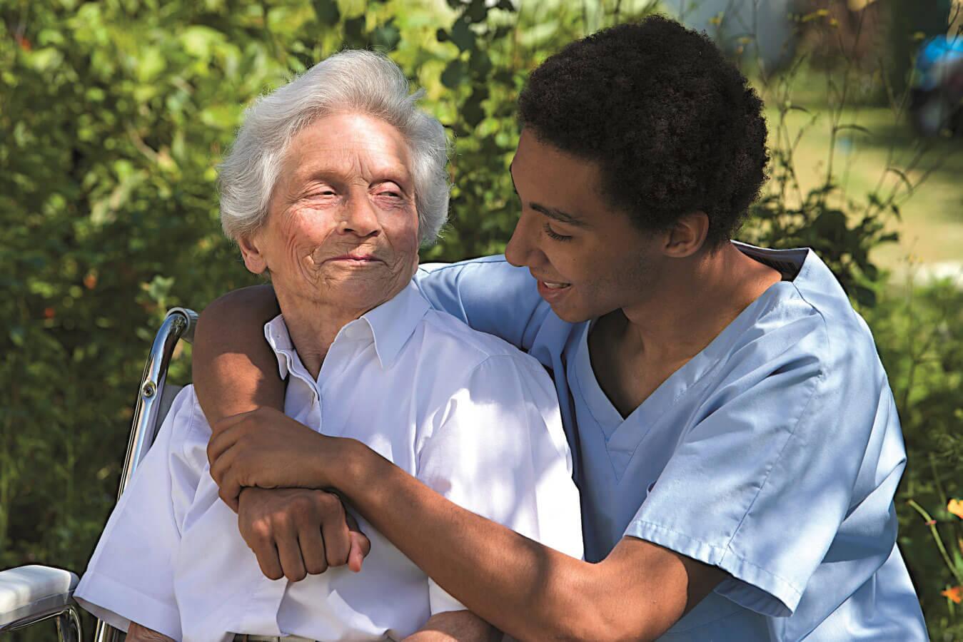 Ältere Dame wird von einer Pflegerin im Park umarmt.