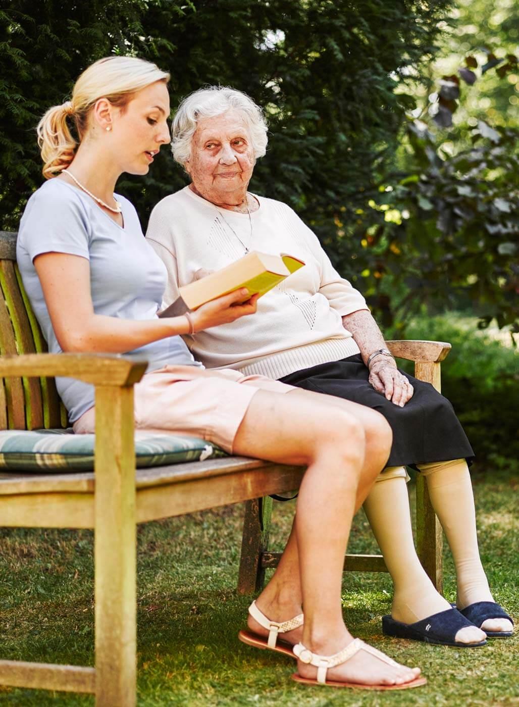 Ehrenamtliche Helferin liest einer älteren Damen im Garten vor.