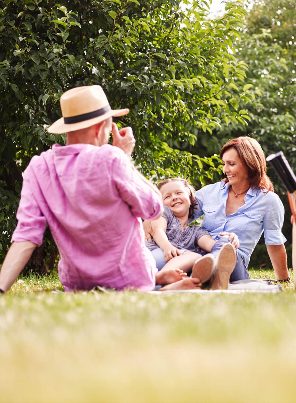 Eltern und Tochter picknicken auf einer Wiese.