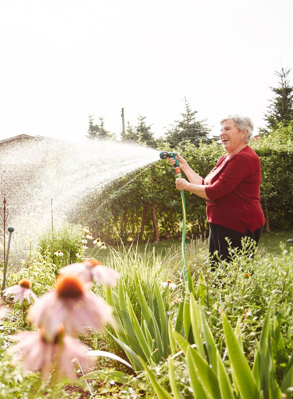 Seniorin wässert ihren Garten.