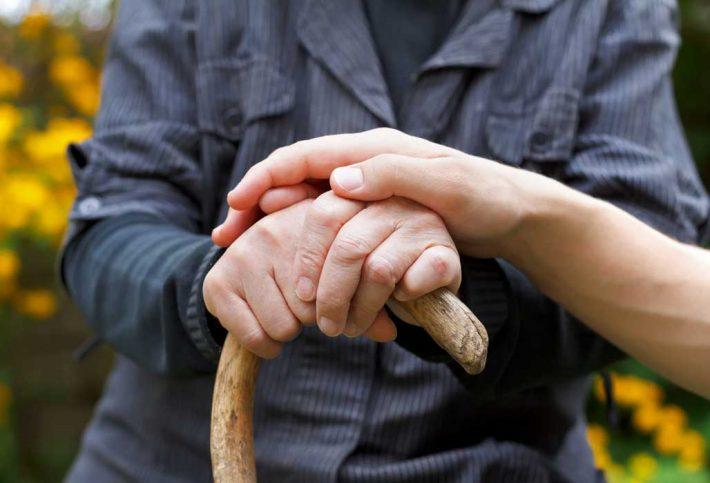 Fachtag Demenz - Hand berührt die Hände eines alten Manns am Gehstock