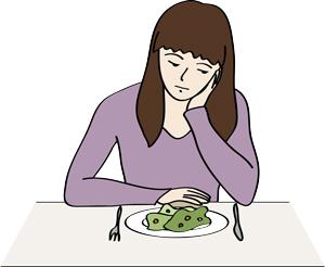 Eine Frau sitzt nachdenklich vor ihrem Essen.