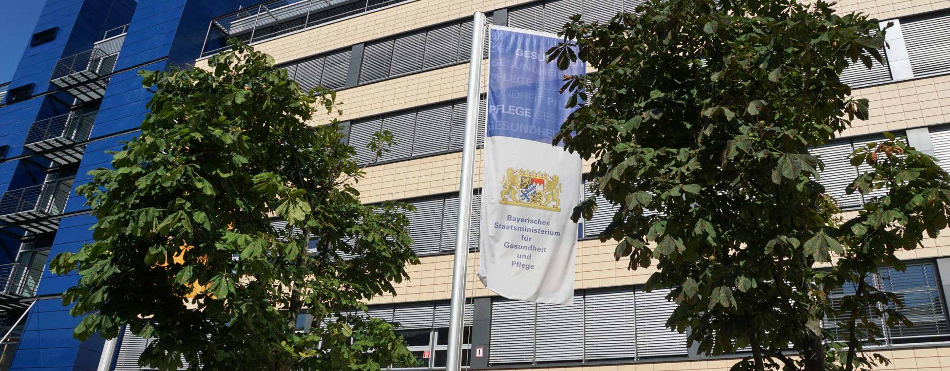 Flagge des Bayerischen Staatsministeriums für Gesundheit und Pflege vor dem Dienstgebäude in München