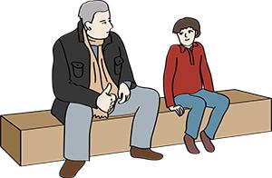 Mann redet mit einem Jungen.