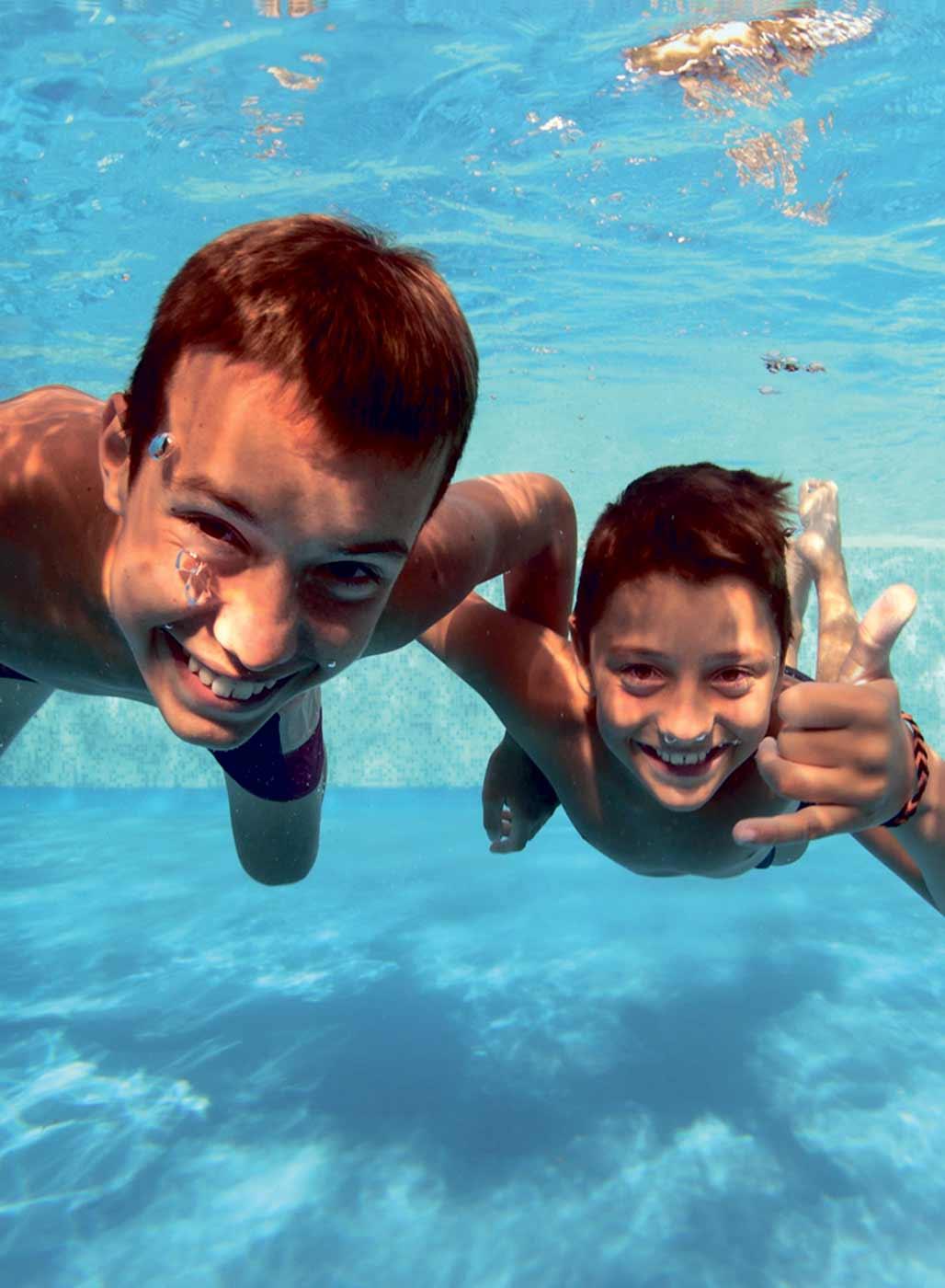 Jungen lachen unter Wasser in die Kamera