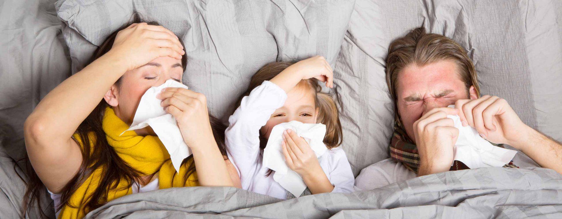 Familie liegt krank im Bett.