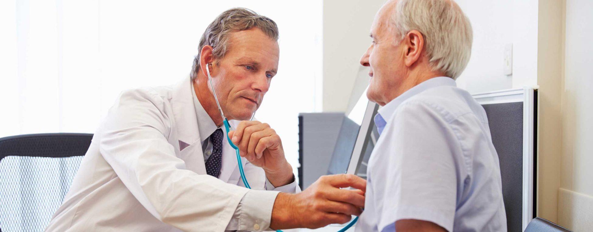 Krebsvorsorge - Arzt untersucht älteren Patienten am Oberkörper mit einem Stethoskop