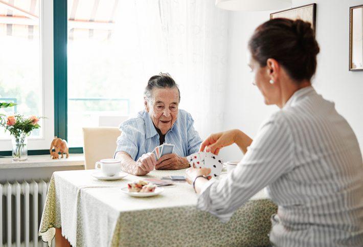 Seniorin und pflegende Angehörige beim Kartenspiel mit Kaffee und Kuchen