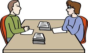 Ein Mann und eine Frau sitzen an einem Besprechungstisch. Vor ihnen liegen viele Papiere.