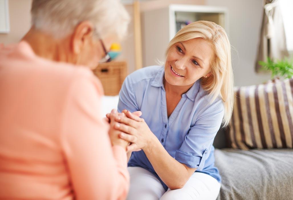 Frau hält einer älteren Dame die Hände