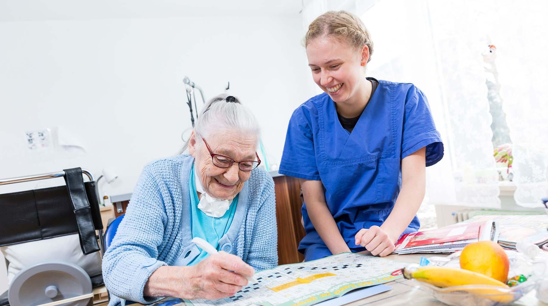Pflegerin löst mit Bewohnerin ein Kreuzworträtsel