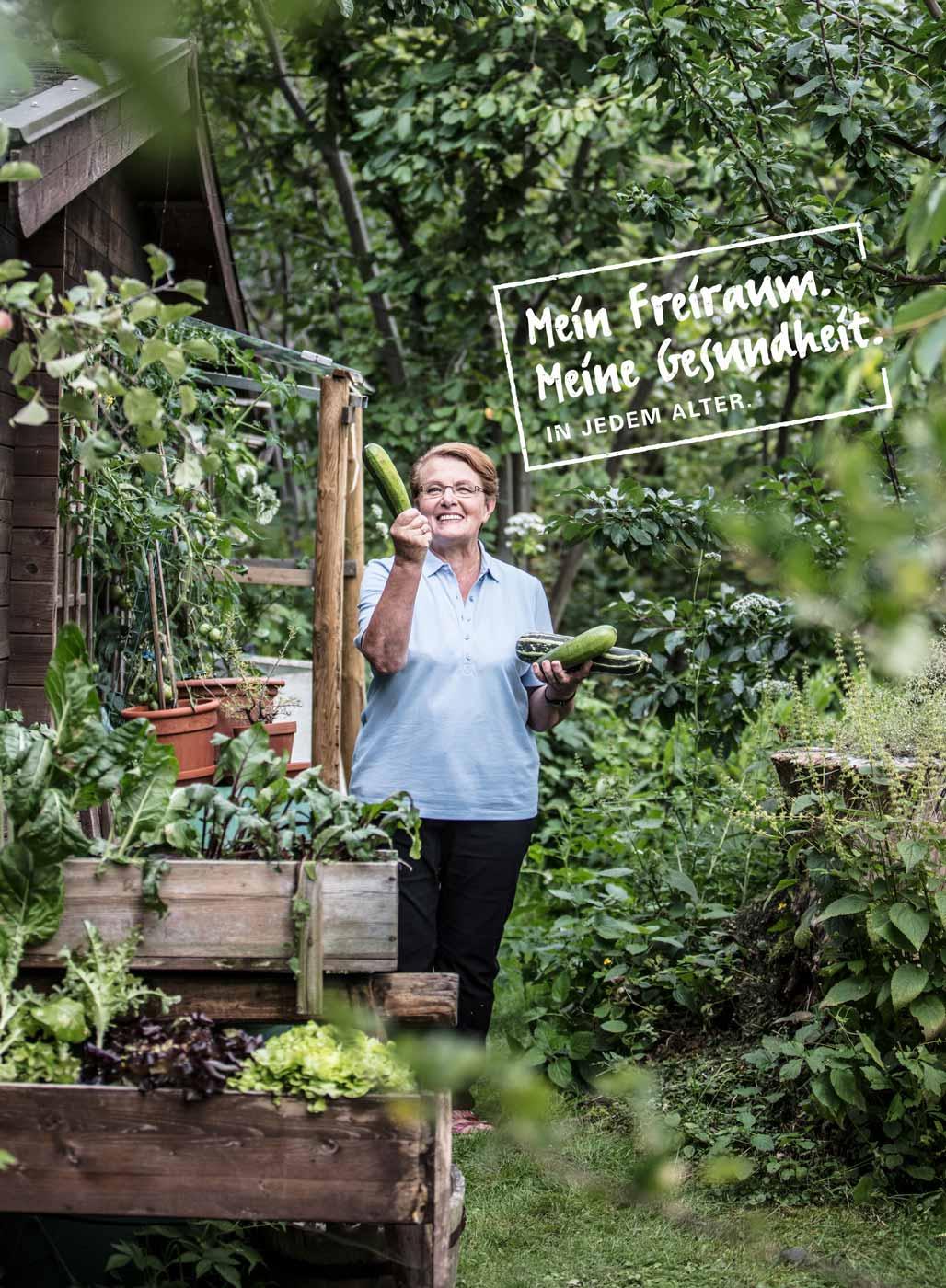 Mein Freiraum. Meine Gesundheit. In jedem Alter. Bild zeigt eine Frau im Garten, die eine Zucchini in der Hand hält.