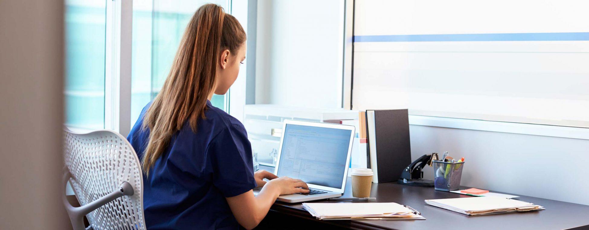 Krankenschwester arbeitet an einem Laptop