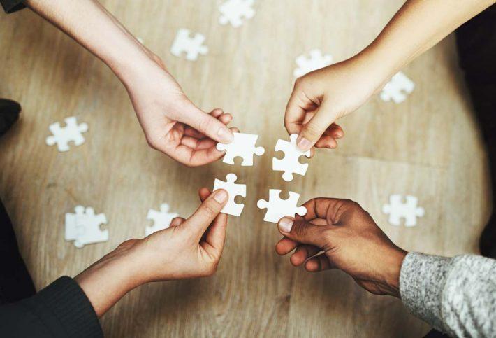 Vier Hände fügen Puzzleteile zusammen