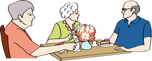 Drei Senioren sitzen am Tisch.