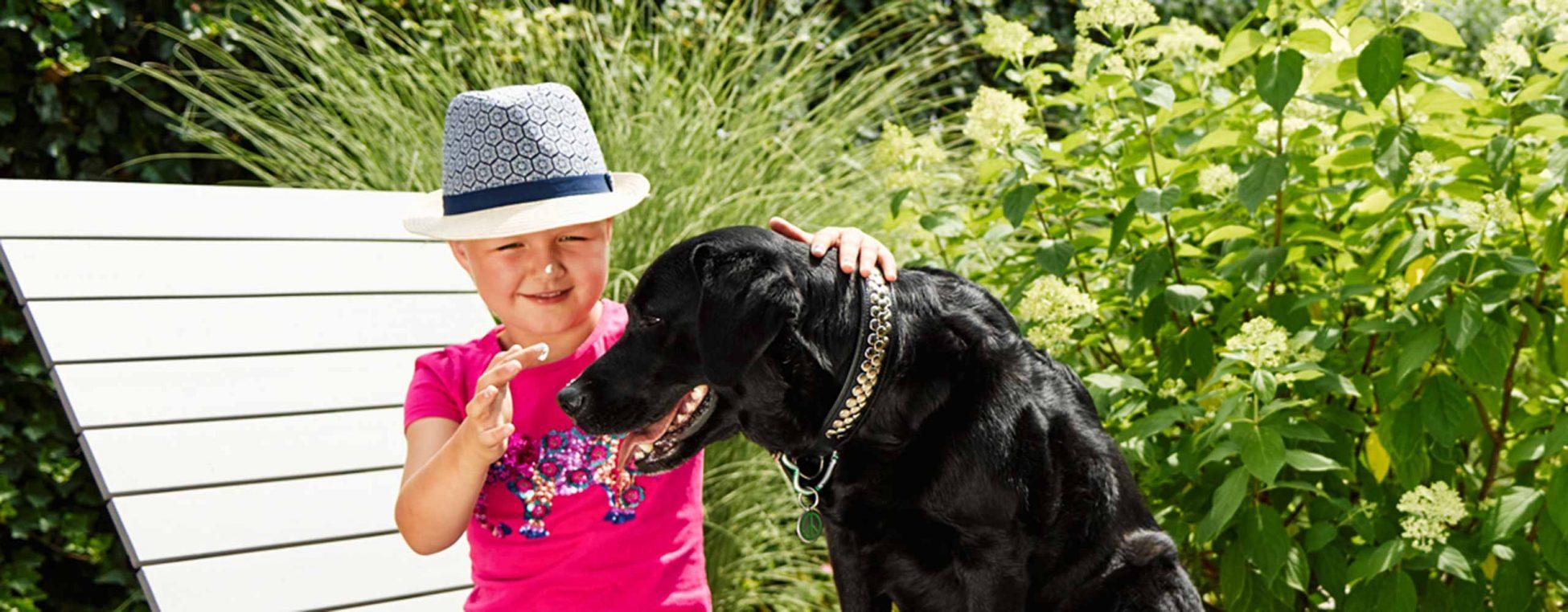 Mädchen macht Hund zum Spaß einen Tupfer Sonnencreme auf die Nase - Sonne(n) mit Verstand
