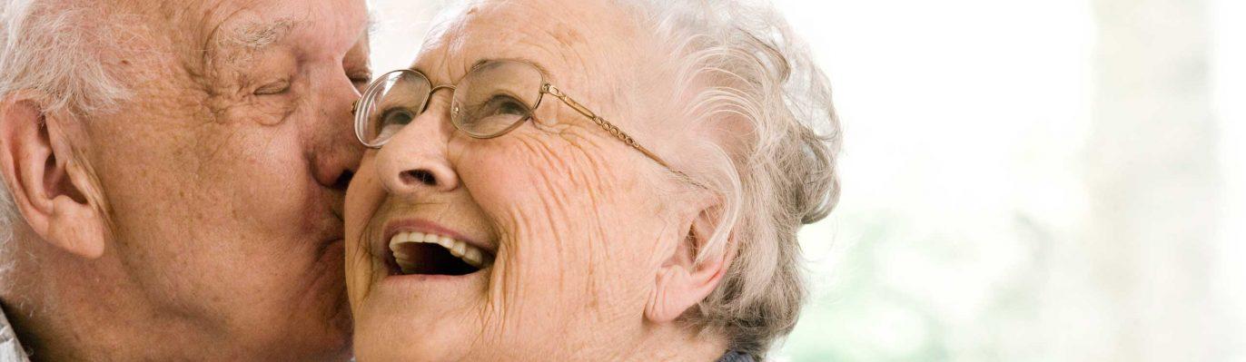 Bayerische Demenzwoche - ein älterer Herr gibt einer älteren Frau einen Kuss auf die Wange
