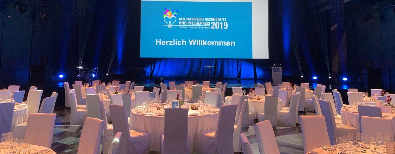 Saal mit Leinwand Herzlich Willkommen beim Bayerischen Gesundheits- und Pflegepreis 2019