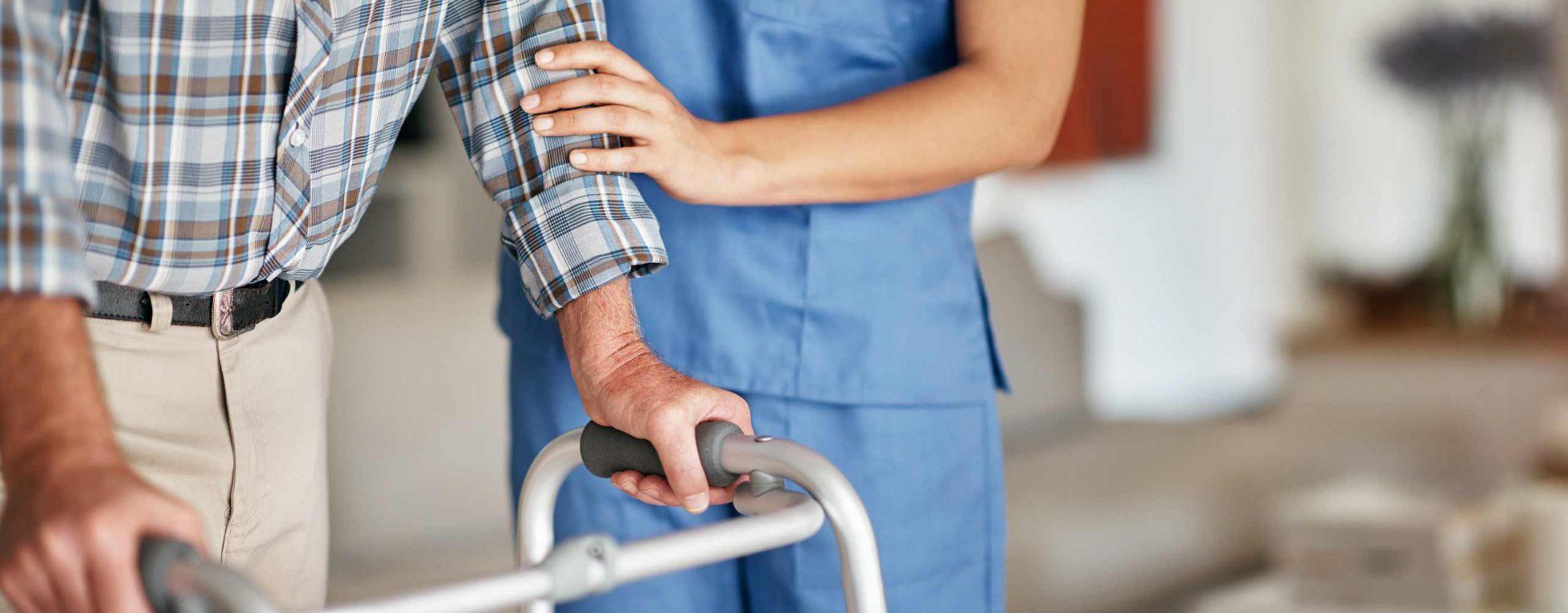 Eine Pflegekraft untersützt einen älteren Mann beim Laufen.