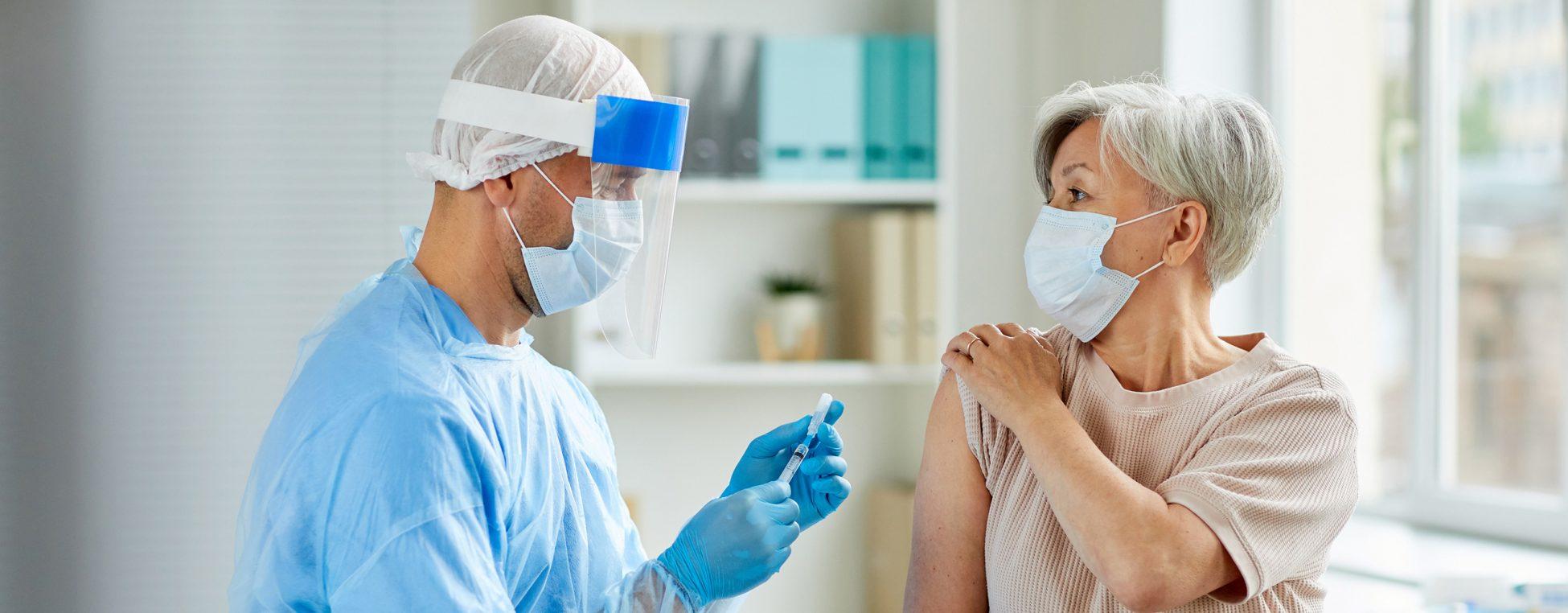 Arzt impft eine Frau.