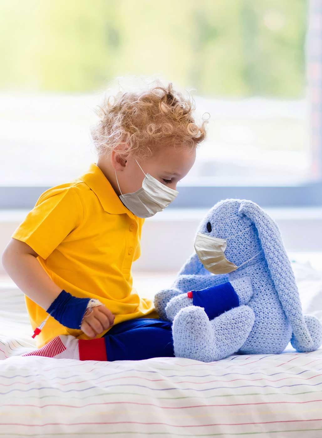 Kleiner Junge im Krankenbett mit Maske und Plüschhasen - Imagebild