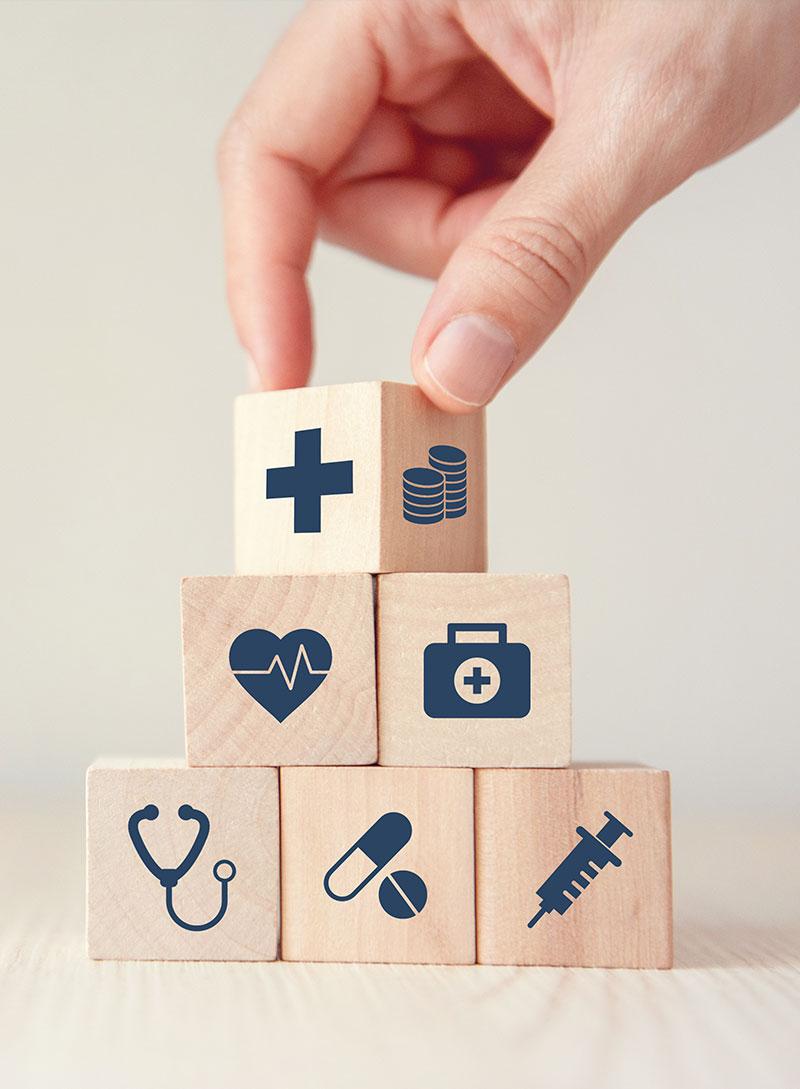 Imagebild zeigt Würfel, die verschiedene medizinische Symbole abbilden und aufeinandergestapelt werden