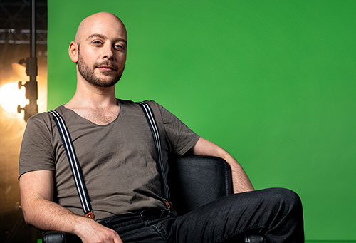 Portrait eines jungen Mannes mit Glatze, der entspannt in einem Sessel sitzt