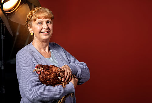 Portrait einer älteren Dame mit Huhn auf dem Arm