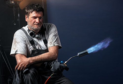 Portrait eines Mannes mittleren Alters in Arbeitskleidung und mit Werkzeug zum Schweißen in der Hand