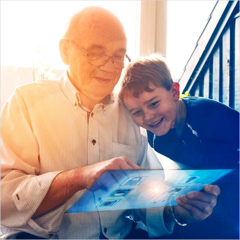 Imagebild zeigt älteren Herren mit kleinem Jungen, die beide auf eine virtuelle Oberfläche schauen und damit ihr Smarthome steuern