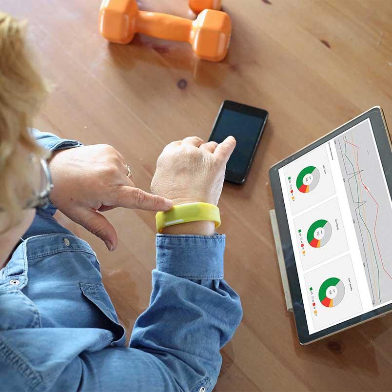Imagebild zeigt Seniorin, die auf ihre Fitnessuhr tippt und vor sich ein Tablet stehen hat, welches eine Datenanalyse anzeigt