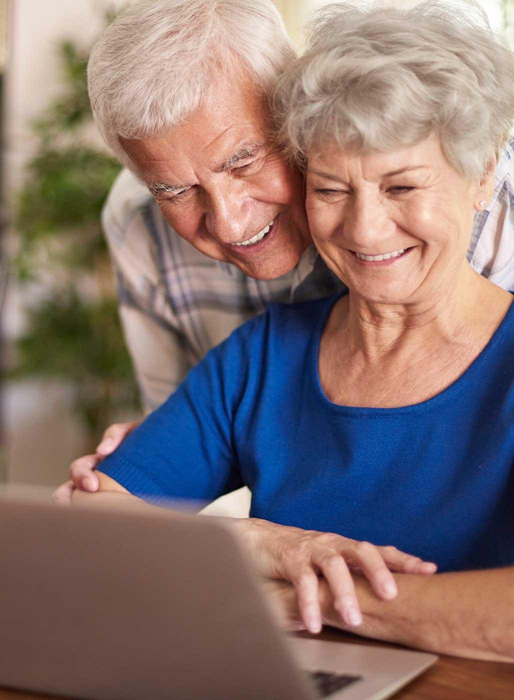 Älteres Paar, dass lächelnd vor einem Laptop sitzt