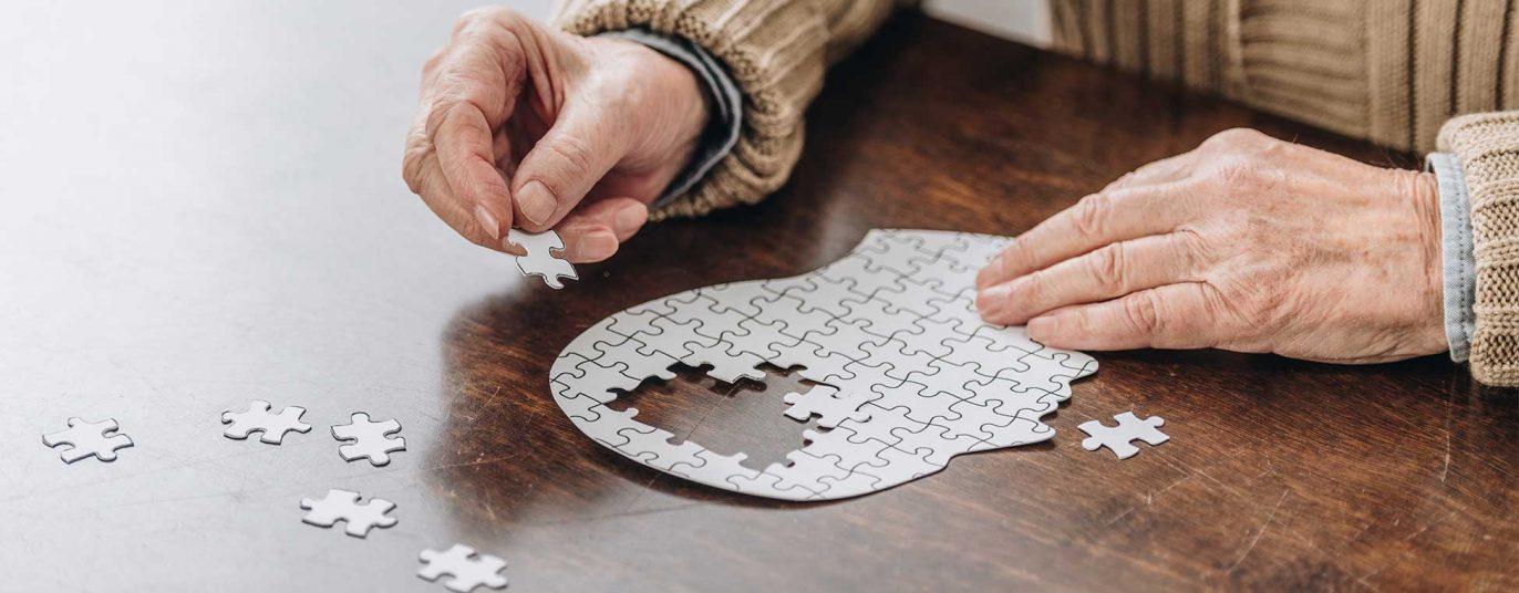 Hände einer älteren Person, die einen Menschenkopf puzzelt; der mittlere Teil des Kopfes ist ohne Puzzleteile