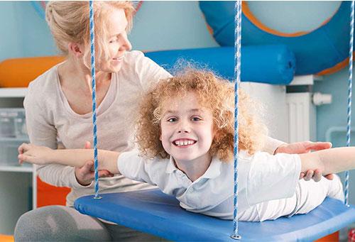 Bild zeigt Kind und Therapeutin in ergotherapeutischer Behandlung
