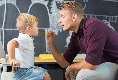 Das Bild zeigt Mann und Kind in logopädischer Behandlung